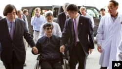 In this photo released by the U.S. Embassy Beijing Press Office, blind lawyer Chen Guangcheng is wheeled into a hospital by U.S. Ambassador to China Gary Locke, right, and an unidentified official at left, in Beijing Wednesday May 2, 2012.