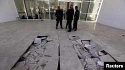 FILE - Policemen near the damaged tiles inside the Bardo museum in Tunis, March 19, 2015.