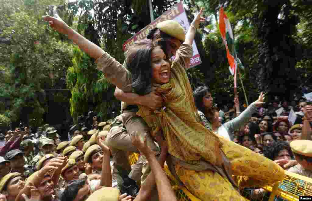 Seorang polisi perempuan berusaha menghentikan seorang anggota All India Mahila Congress, sayap perempuan partai Kongres, yang mencoba melewati barikade, ketika demo menentang Perdana Menteri India Narendra Modi berlangsung di New Delhi.