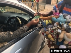 A vendor sells dolls at an intersection of Harare's streets, Oct. 2017.