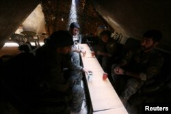 FILE - Fighters of the Syria Democratic Forces drink tea as they rest inside a shelter in northern province of Raqqa, Syria.