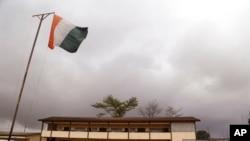 Un drapeau ivoirien flotte devant un bureau de vote d'Abidjan, le 25 octobre 2015.