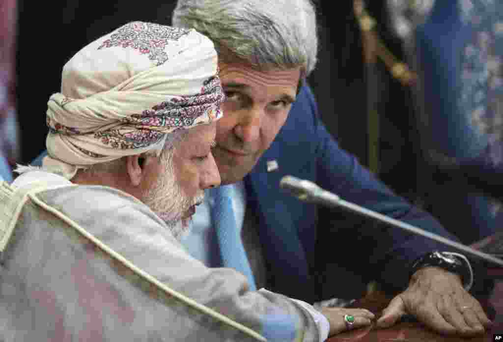 Oman's Foreign Minister Yusuf bin Alawi bin Abdullah and U.S. Secretary of State John Kerry talk before a meeting of the Gulf Arab region, Jeddah, Saudi Arabia, Sept. 11, 2014.