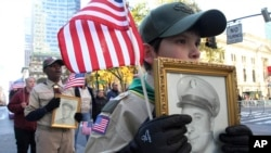 Veterans Day Parade Boy scout Mateo de La Roche, 11, of Carteret, New Jersey, foreground, holds an image of World War II veteran Michael Wozny, as he takes part in the Veterans Day Parade along New York's Fifth Avenue Sunday, Nov. 11, 2018.