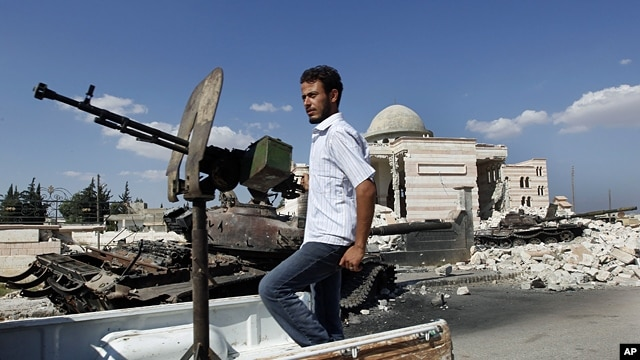A Free Syrian Army soldier drives by a Syrian tank and a mosque, which were destroyed during fighting with government forces, in Azaz, on the outskirts of Aleppo, Sept. 23, 2012.
