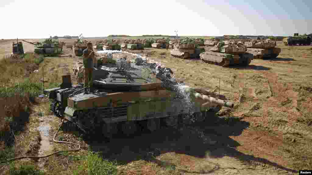 An Israeli soldier washes a tank at a staging area near the border with the Gaza Strip, Aug. 10, 2014.