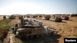 Một binh sĩ Israel rửa xe tăng tại nơi đóng quân gần biên giới với Dải Gaza, ngày 10 tháng 8, 2014.