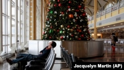 FILE - Andres Alarcon, 29, of Colombia and a student at Washington's Howard University, sleeps by a Christmas tree inside of Reagan National Airport in Washington, on Saturday, Dec. 19, 2009.