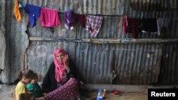 Seorang wanita Palestina duduk dengan cucunya di kamp pengungsi Khan Younis di Jalur Gaza selatan, 11 Juli 2017.