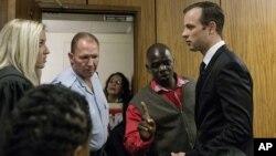 Oscar Pistorius, à droite, parle à son avocate à Pretoria, Afrique du Sud, le 18 avril 2016.
