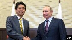 Presiden Rusia Vladimir Putin (kanan) berjabat tangan dengan PM Jepang Shinzo Abe di Sochi, Rusia (6/5).