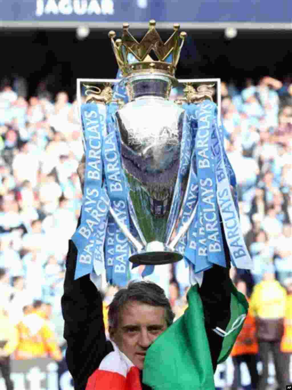 Manajan kungiyar Manchester City, Roberto Mancini, dauke da kofin zakarun wasannin lig-lig na Ingila, Premier League, a bayan da 'yan wasansa suka doke Queens Park Rangers suka lashe wannan kofi a ranar lahadi 13 Mayu, 2012 a filin wasa na Etihad dake Man