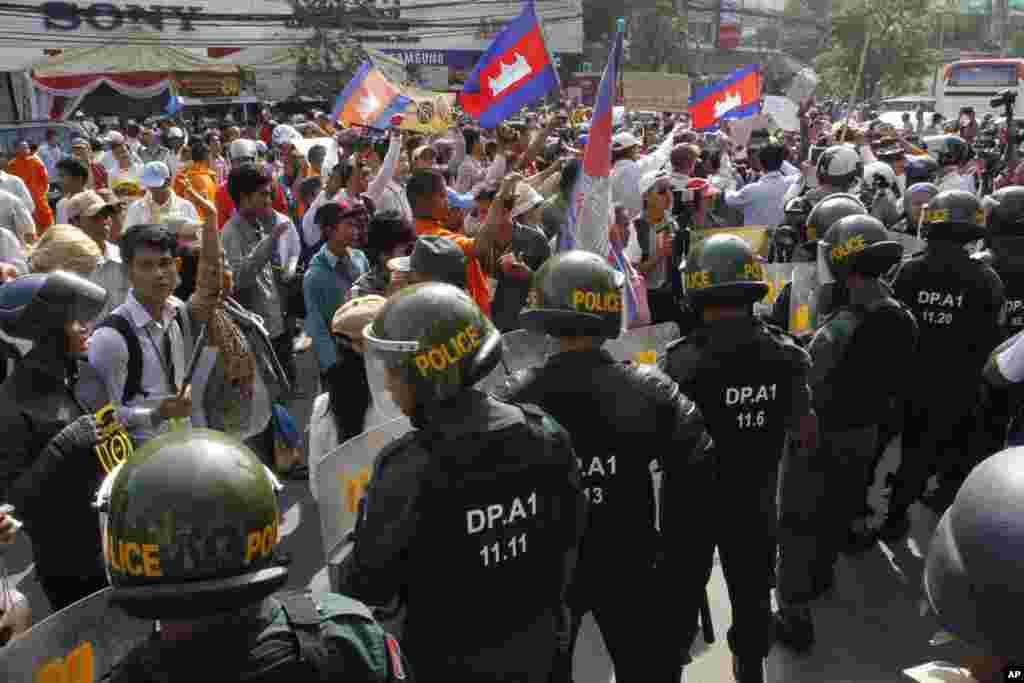 Polisi anti huru hara memblok demonstran yang dipimpin oleh pembela HAM Mam Sonando, yang meminta pemerintah memberikan ijin pendirian saluran televisi baru di Phnom Penh, 27 Januari 2014.