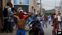 Un manifestante usa una camiseta como una máscara improvisada para protegerse del gas lacrimógeno durante enfrentamientos con la policía y partidarios del gobierno en el distrito Monimbo de Masaya, Nicaragua, el sábado, 12 de mayo, de 2018.