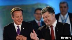 Presiden Ukraina Petro Poroshenko (kanan) dan PM Inggris David Cameron berbincang-bincang dalam diskusi mengenai NATO-Ukraina di Celtic di Newport, Wales, (4/9/2014).
