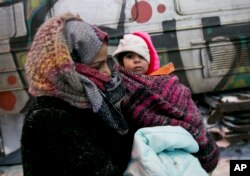A migrant mother holds her baby walking towards a passenger train in Presevo, close to the Serbian border with Macedonia, 300 kilometers southeast of Belgrade, Serbia, Jan. 18, 2016.