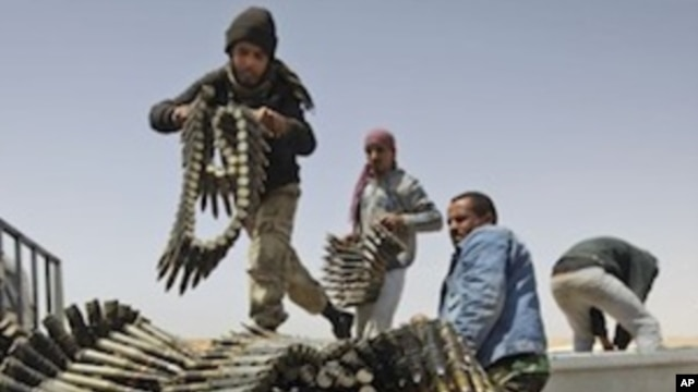 Libyan rebel fighters load a truck with ammunition on the outskirts of Ajdabiya, Libya, Saturday, April 16, 2011.