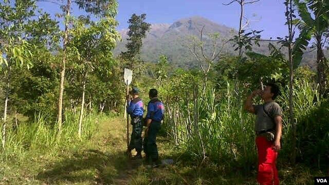 Relawan dan anggota tim SAR meretas jalan menuju Gunung Agung, Bali, untuk memadamkan kebakaran hutan. (Foto: VOA/Muliarta)