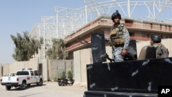 Iraqi security forces guard the entrance to a sports complex being built by a Turkish construction company, in the Shiite district of Sadr City, Baghdad, Iraq, Wednesday, Sept. 2, 2015.