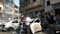 Warga berkumpul di lokasi ledakan dua bom yang meledak di distrik Zahra, Homs (29/4). (AP/SANA)