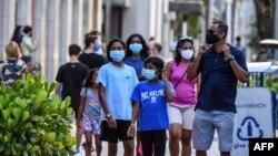 Satu keluarga mengenakan masker saat berjalan-jalan di Miami Beach, Florida, 29 Juni 2020.