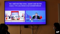 Nepalese government officers watch a live telecast of a joint announcement on the height of Mount Everest, in Kathmandu, Nepal, Tuesday, Dec. 8, 2020. China and Nepal have jointly announced on Tuesday, Dec. 8, 2020, a new height for Mount Everest, ending