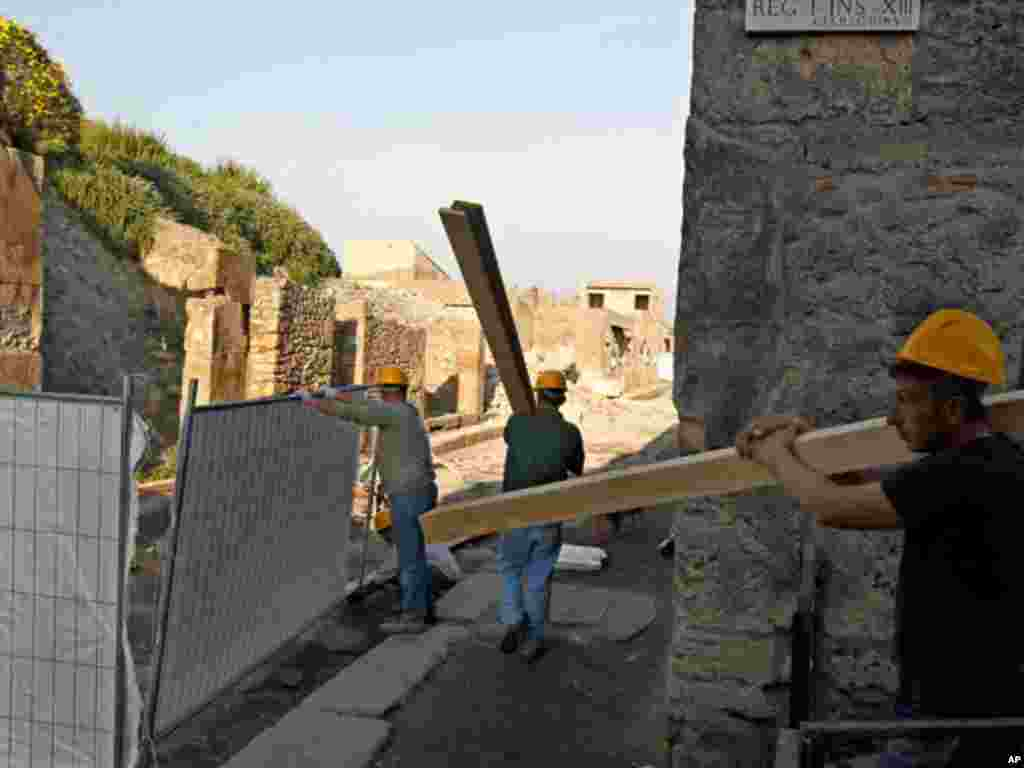 """Workers repair the 2,000-year-old """"House of the Gladiators"""" in the ruins of ancient Pompeii. (Reuters)"""