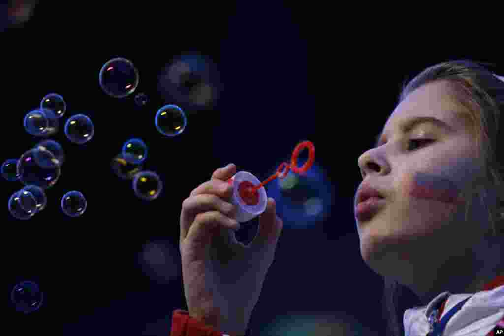 A girl, the Russian flag painted on her face, blows bubbles as she waits for the start of the closing ceremony of the 2014 Winter Olympics in Sochi, Feb. 23, 2014.