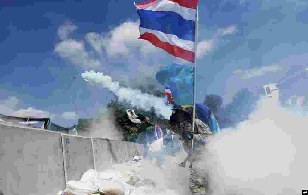 Demonstran anti-pemerintah melemparkan kembali kaleng gas air mata yang dilemparkan oleh polisi anti huru-hara di Bangkok (1/12).
