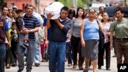 Welsar Nazario lleva el ataúd de su sobrino de cinco meses, Alezandro Macario, quien murió en el deslave, hacia un cementerio en las afueras de Ciudad de Guatemala, el sábado, 3 de octubre de 2015.
