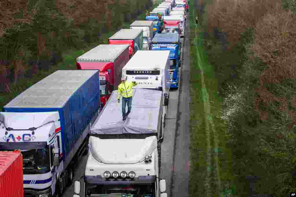 Drivers stand among trucks on the E411 highway from Brussels to Luxembourg as they protest against road charging, near Spontin, Belgium.