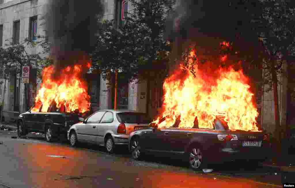 Cars are set on fire by protesters during a rally against Expo 2015 in Milan, Italy. Italy opened the Expo on Friday, torn between hopes that the showcase of global culture and technology will cheer up a gloomy national mood and fears that it will be overshadowed by scandal, delays and street protests.