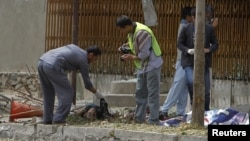 Afghan policemen investigate at the site of suicide attack in Kabul, September 8, 2012.