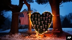 FILE - A makeshift memorial with crosses for the victims of the Sandy Hook Elementary School shooting massacre stands outside a home in Newtown, Conn., on the one-year anniversary of the shootings, Dec. 14, 2013.