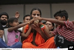 FILE - Indian yoga guru Baba Ramdev drinks a fruit juice offered by children to break his fast in New Delhi, India, August 14, 2012.