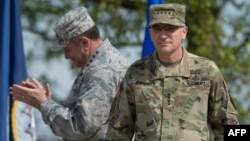 U.S. General Philip Breedlove (L) applauds as he stands next to U.S. General Curtis Scaparrotti during a ceremony on May 3, 2016, at the Patch Barracks in Stuttgart, southern Germany. During a ceremony, Breedlove handed over the U.S. European command to S