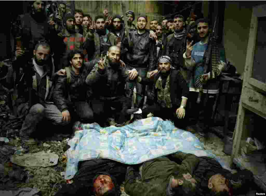 Free Syrian Army fighters pose next to bodies in Homs, March 3, 2013.
