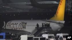 Para penumpang pesawat maskapai Turki Pegasus meninggalkan pesawat di bandar udara Sabiha Gokcen di Istanbul, Turki (7/2) menyusul ancaman bom. (AP/Emrah Gurel)