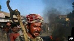 24일 인도 아쌈주 샤무쿨리 마을 주민들이 도로를 점거한 채 분리주의 폭동에 항의하고 있다.