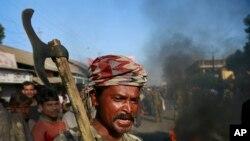Un colon tribal indien crie des slogans comme il bloque une route avec d'autres manifestants en signe de protestation contre l'attaque par un groupe séparatiste dans le village indigène Shamukjuli dans l'Etat d'Assam en Inde, le 24 décembre 2014.