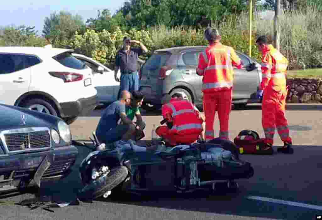 """Ambulance personnel tend to a man lying on the ground, later identified as actor George Clooney, after being involved in a scooter accident in the near Olbia, on the Sardinia island, Italy. Actor George Clooney was taken to the hospital in Sardinia and released after being involved in an accident while riding his motor scooter, hospital officials said. """"He is recovering at his home and will be fine,"""" spokesman Stan Rosenfield told The Associated Press in an email."""