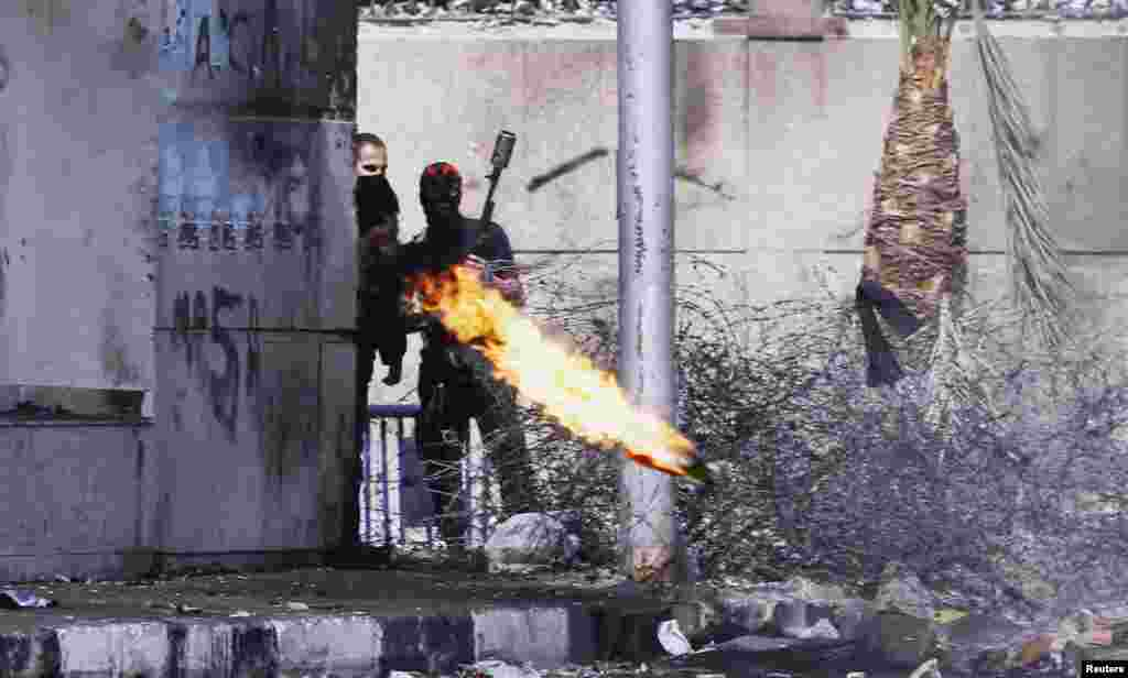 A protester, opposing Egyptian President Mohamed Morsi, throws a Molotov cocktail at riot police, during clashes in front of Security Directorate in Port Said city, 170 km (105 miles) northeast of Cairo.