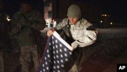 یک سرباز امریکایی در حال جمع کردن بیرق ملی ایالات متحده از پایگاه نظامی در عراق