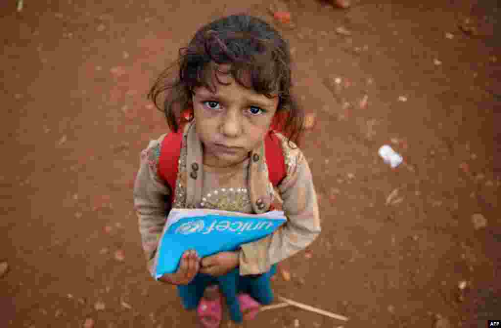 "A Syrian child who fled with her family from the northern countryside of Hama, holds a book in the yard of the makeshift school of ""Zuhur al-Mustaqbal"" (in Arabic ""Flowers of the Future"") in al-Jeneinah camp for displaced people in the village of Atme, in Syria's mostly rebel-held northern Idlib province."