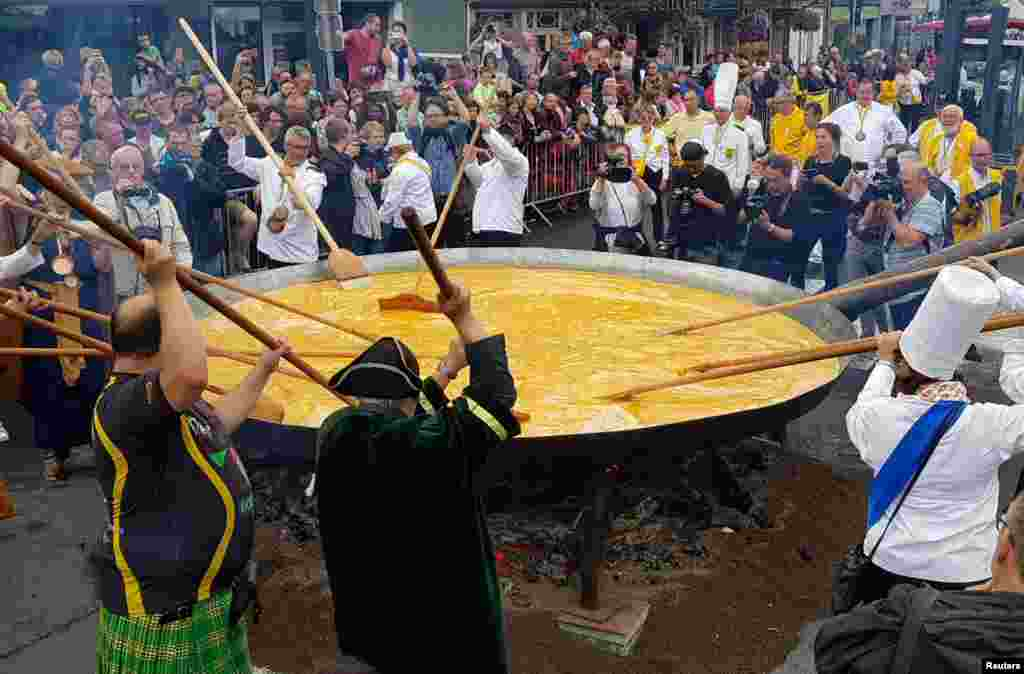 Members of a worldwide fraternity devoted to an egg dish prepare a traditional giant omelette made with 10,000 eggs in Malmedy, Belgium.
