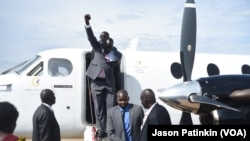 Second-in-command of South Sudan's rebels, Alfred Lado Gore, raises his fist after landing in the capital Juba, after more than two years in exile, April 12, 2016. Rebel leader Riek Machar is scheduled to return on April 18.