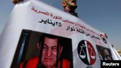 2011年埃及革命期间有亲属被打死的一位男士举着穆巴拉克的画像抗议。(2014年9月27日)