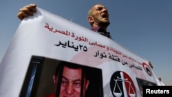 FILE - A man whose relatives were killed during the 2011 Egyptian revolution holds a banner with pictures of former President Hosni Mubarak, Sept. 27, 2014.