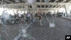 Penyelidik Suriah terlihat dari balik kaca depan bus yang rusak terkena ledakan di daerah Midan, Damaskus, Jumat (27/4).