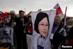 FILE - Members of the Taiwanese community in Paraguay hold an image of Taiwan's President Tsai Ing-wen upon her arrival at the Silvio Pettirossi International Airport in Luque, Paraguay, Aug. 14, 2018.